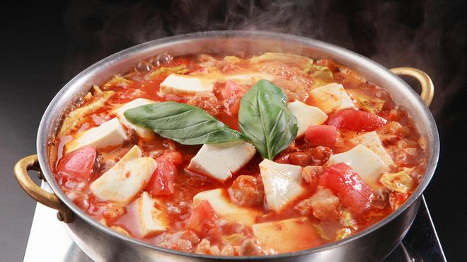 ぶあいそ - 料理写真:人気メニュー「トマトもつ鍋」〆のチーズ雑炊はまるでリゾットのよう。
