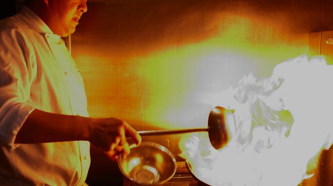 MASA'S KITCHEN - 内観写真:鍋を振る鯰江真仁シェフ。毎日オープンキッチンで、お客様の顔を見ながら料理を作り続ける