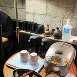はら凹 - フロアの中央に炊飯器と漬け物、お茶がある