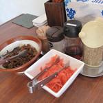 らーめん神 - 卓上にはスリゴマやコショウの他、取り放題の紅しょうがと辛子高菜。