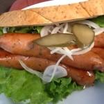 腸詰屋 - 2012/10 ガーリックソーセージを半分にしたものが4つ(すなわち、2本)、それにオニオンとピクルスをパンに挟んだもの。ニンニクの風味で食欲をそそります