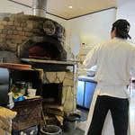 檪の丘 - 石焼釜でピザを焼くスタッフの姿が見えます