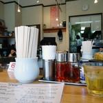 東京担担麺本舗 ゴマ屋 - コの字カウンターのローアングル。