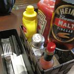 ワッツカフェ - 卓上セット。 ケチャップ・マスタード・タバスコの他にモルトビネガーもあります。 フィッシュ&チップスのように、フレンチフライにかけるのでしょうか。 それからフォーク・ナイフの他にお箸まであります。