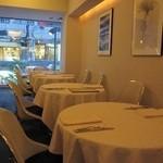 ヴィノ・ヒラタ - 白を基調としたテーブル席。夜は、ちょっと暗い