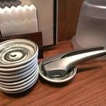 麺や純氣 - 生ニンニクのクラッシャー、餃子のタレを入れる小皿、ナプキンです。