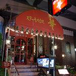 """ステーキハウス華 - 目印の赤い""""華""""の看板と入り口"""