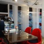 De PLUS CAFE - レースのカーテン(仕切)越しに、童夢-零(ドウム・ゼロ)の写真が少し見えます。
