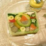 29055610 - オードブル 野菜のテリーヌ 椎茸 青と黄のズッキーニ ヤングコーン 牛蒡 ホウレン草 人参 インゲン豆 回りをキャベツで包んで キウイを練り込んだ岩塩とブラックペッパー