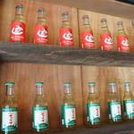 ドラゴン - お店の壁に並んだ、赤のカープチャイダーと、緑のちゃーダーのビン達