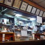 北京亭 - 厨房の様子。カウンター席の上に整然と並ぶ額縁に注目☆