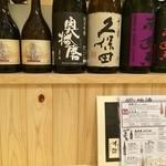 万彩 - カウンターの上に並ぶ地酒の瓶