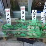 水沼さざえ店 - 店の前の水槽に貝類が浸かっています