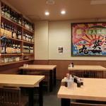味菜芳文 - テーブル席。壁面にお酒がいっぱい。