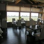 Cafe Rire - 全席、白い1人用ソファ。大きな窓からはサッカー場と、その向こうにヨットハーバーが見える。