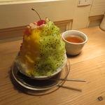 39857686 - 本日のかき氷:キウイ生スクイーズ、マンゴー生スクイーズ、プラムソース、白いんげん豆、                       アプリコットソース、さくらんぼ全がけ、温かい朝宮ほうじ茶付き1