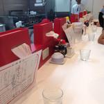 麺毅家 - 赤がポイントカラーのモダンな店内