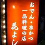 花よし - お店の看板です。おでん・串かつ 一品料理の店 花よし って書いていますね。オレンジ色の電飾看板が目立っていますよ。