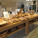 BREAD&DISHES MUGINOKI - 9時過ぎの訪問だったんですが既にお店の奥にあるカフェは食事を楽しむ主婦の皆様で賑わってました。   私はパンのみの購入だったんで並んだパンの中からゴルフの後のおやつ用にパンを選んでみました。