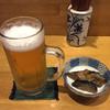 よろずや - 料理写真:晩酌セット(2ドリンクとお通しと煮込み・1,500円)の1杯目の生ビール(2杯目の生でした。) お通しはナスの味噌炒り。おふくろの味って感じ。