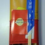九十九島 海遊 - 海遊のレモンステーキ弁当です。 長方形の容器に柿色と赤色のパッケージで包まれています。 そして、レモンステーキの由来の紙と箸が乗っかっています。