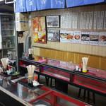 久村の酒場 - コの字型のカウンター。ガラスケースに料理が入っている。