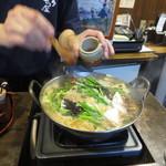 元祖博多麺もつ屋 - 出来上がり前にお好みで胡麻と鷹の爪を投入