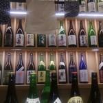 61444942 - 通されたのが、入り口付近にあるカウンター席、目の前には、日本酒の一升瓶がイッパイ。