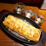 地酒喝采 かも蔵 - 栃尾ピザ(¥771)。新潟名物・栃尾の厚揚げを洋風に仕上げた一品
