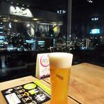 さわら - 窓際のフリーテーブルよりガラスに映るのは「さわら」。生ビール税込480円