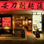 西安刀削麺酒楼 - 赤い看板と石造のオブジェが目印♪